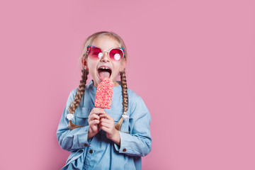 little cheerful girl in sunglasses with ice cream on pink background Fototapete
