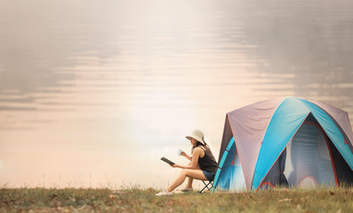Foto op Canvas Kamperen asian woman camping and tent outdoors near the lake.