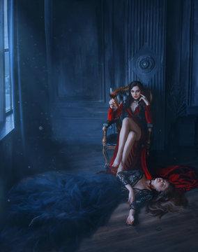 Art evil woman vamp. Red long dress sits in vintage armchair. Holding glass Blood wine. at feet lies sleeping beauty dead princess. black lush dress. Bloody vampire bite. backdrop medieval room night