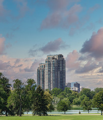 Fototapete - A modern high rise condominium building rising into sky beyond a green park