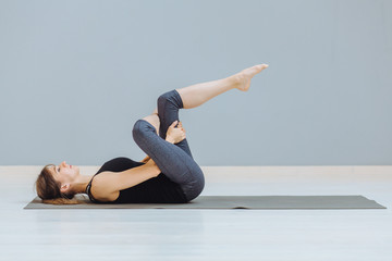 Relaxing back pain exercise concept. Attractive sportive woman doing pilates exercise lying on yoga mat at empty room at grey wall ackground.