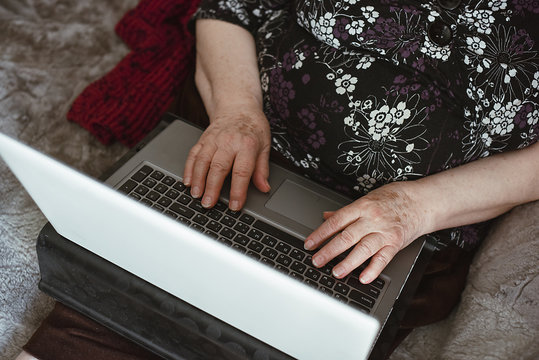 Beautiful hands of a old woman. Old woman's hands with wrinkles working on laptop. Work from home for pensioners