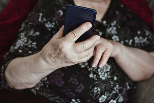 Beautiful hands of a old woman. Old woman's hands with wrinkles touching screen her smartphone