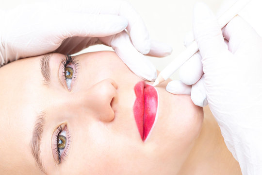Young woman having permanent makeup on her lips at the beauticians salon. Permanent Makeup (Tattoo). drawing a contour with a white lip pencil