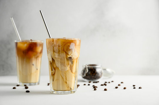 Two glasses of iced coffee on a light concrete table. Frozen swirls of milk. Horizontal orientation, copy space.