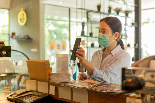 Woman customer with protective mask paying bill by cell phone in cafe.