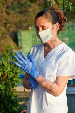 Medical worker wearing Coronavirus face protective mask and blue gloves in the exterior of the Hospital