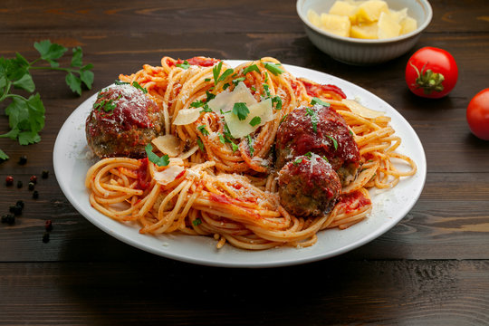 Traditional Italian spaghetti with meatballs and parmesan in tomato sauce on a white bowl. American family meal on a table.