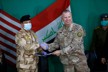 U.S. Brigadier General Vincent Barker shakes hands with Iraqi General Mohammed Fadel during the hand over of US-led coalition forces to Iraqi Security Forces at Qayyarah Airfield West in the south of Mosul