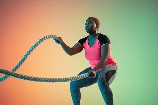 Young african-american plus size female model's training on gradient background in neon light. Doing workout exercises with the ropes. Concept of sport, healthy lifestyle, body positive, equality.