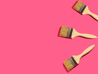 Paint varnishing brushes with wooden handle scattered on fuchsia pink background. Interior design...