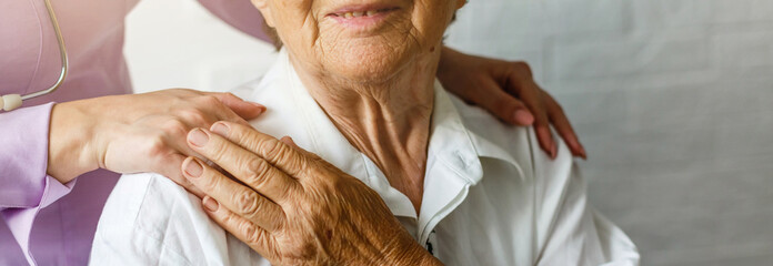 Elderly female hand holding hand of young caregiver at nursing home.Geriatric doctor or...