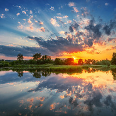 Beautiful sunset, sky with clouds above lake.