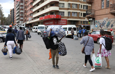 A man carries luggage as he walks to a taxi rank as residents of a number of African cities where the coronavirus is spreading are heading to the countryside to try to escape from the disease, in Johannesburg