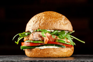 Vegetarian American Cuisine. Burger with red fish salmon, arugula, cucumbers and tomatoes, white sauce. Burger on a black background. background image, copy space text