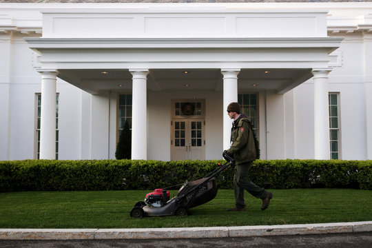 A National Park Service gardner mows the lawn as Trump prepared to join G20 leaders on a conference call about the global coronavirus response at White House in Washington