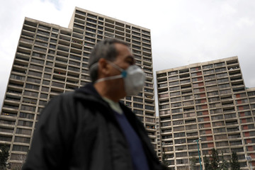 A man wearing a protective face mask walks next to buildings where people stay home, amid fear of coronavirus disease (COVID-19), in Tehran