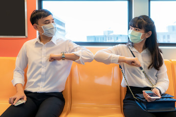 Elbow bump is new novel greeting to avoid the spread of coronavirus. Two Asian business friends meet in subway. Instead of greeting with a hug or handshake, they bump elbows instead.