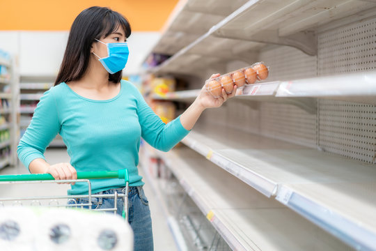 Asian woman pick up last egg pack at Supermarket empty shelves amid COVID-19 coronavirus fears, shoppers panic buying and stockpiling toilet paper preparing for a pandemic.