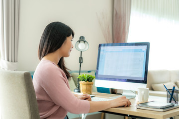 Young asian businesswoman using computer checking e-mail work from home for protect virus and take care of their health from COVID-19. Working at home and social distancing concept.