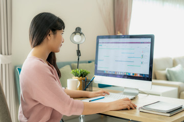 Young asian businesswoman using computer work from home for protect virus and take care of their...