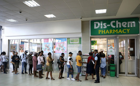 Shoppers queue outside a South African drugstore chain Dis-Chem Pharmacies ahead of a nationwide lockdown for 21 days to try to contain the coronavirus disease (COVID-19) outbreak, in Johannesburg