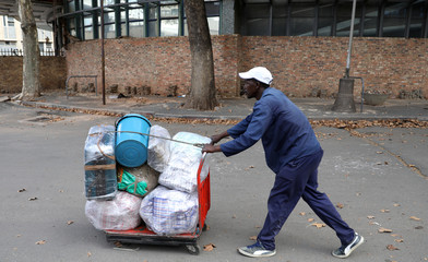A man pushes a trolley loaded with his luggage at Park Station ahead of a nationwide lockdown for 21 days to try to contain the coronavirus disease (COVID-19) outbreak, in Johannesburg