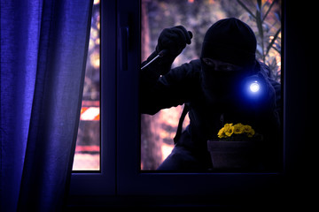 Hooded burglar forcing the window frame - Silhouette of thief with screwdriver and flashlight is breaking into the apartment - Concept of intrusion and danger view from indoor dark shaded image - fototapety na wymiar