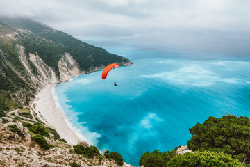 Summer season activity. Glider flying over beautiful Myrtos beach. Kefalonia island, Greece. Amazing water colors and mountain coastline