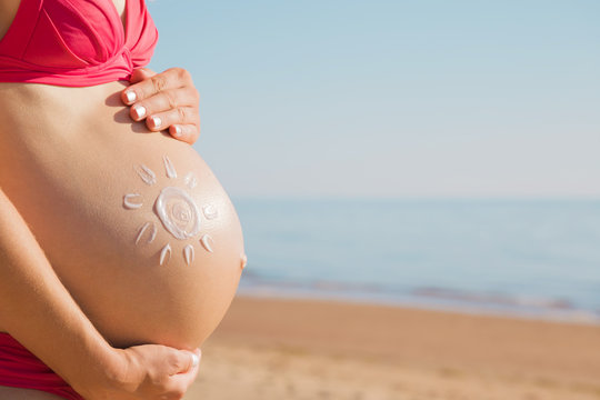 Sun shape created from sunscreen lotion on big belly. Young woman standing at beach. Care about skin protection during sunbathing in pregnancy time. Hot day. Closeup. Copy space. Empty place for text.