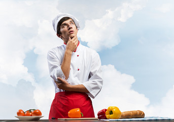 Young male chef standing with folded arms