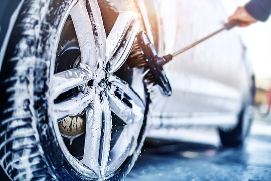 Car wheel wash. Car cleaning with water jet. Car rim or aloy washing close up.