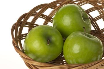 Granny Smith Äpfel im Korb auf einem weissen Hintergrund freigestellt.