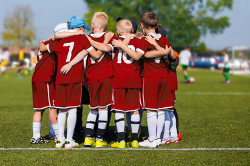 Boys in Sports Team on School Soccer Field. Children Doing Sports in School Team. Kids Team Huddling and Motivating Each Other Before the Tournament Match. Players in Red Jersey Uniforms