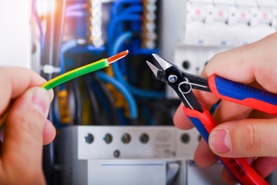 Electrician cutting wires detail.