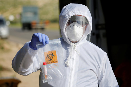 A member of medical staff holds a sample collected from a Palestinian worker at a coronavirus disease testing site, in the Israeli-occupied West Bank