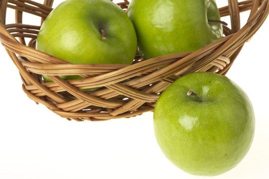Ein Granny Smith Apfel und weiter im Korb auf einem weissen Hintergrund freigestellt.