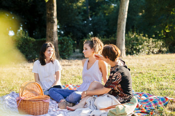 Mother and two daughters make picnic in a park at sunset in summer - Millennials having fun together