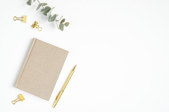Flat lay home office desk. Female workspace with paper notepad and golden accessories on white background. Top view feminine workplace