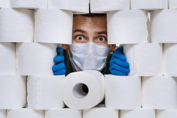 Scared young man in protective mask and gloves is looking out from toilet paper wall, stocking up for home quarantine from coronavirus. Concept of lack of toilet paper in stores due to Covid-19 panic.