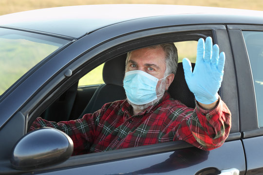 Adult driver with protective surgical mask and gloves gesturing, waving with or shoving stop sign  through window, corona virus protected person