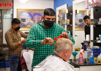 Customers get a haircut ahead of a nationwide 21-day lockdown in an attempt to contain the coronavirus disease (COVID-19) outbreak in Waterfall