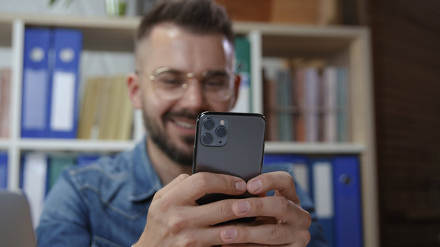 Hipster young joyful man in glasses laughing of fun internet content using modern smartphone relaxing in office space.