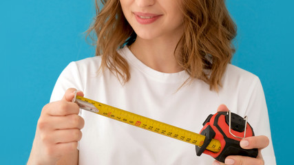 Woman laughs at a small size and enlarges it to a larger. Female in white t shirt unrolling construction measuring tape against blue background