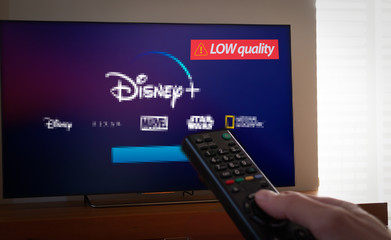 Barcelona, Spain. January 2019: Man holds a remote control With the new Disney plus screen pixelated on TV