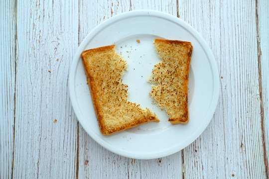 Half slice of white bread on plate, top view