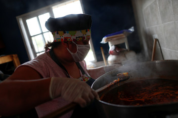 A volunteer wearing a face mask looks at the stew that she's preparing for low-income people at a soup kitchen during the spread of the coronavirus disease (COVID-19), in Florencio Varela, in the outskirts of Buenos Aires
