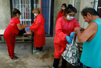 Volunteers wearing a face masks give stew in plastic containers to low-income people at a soup kitchen during the spread of the coronavirus disease (COVID-19), in Florencio Varela, in the outskirts of Buenos Aires
