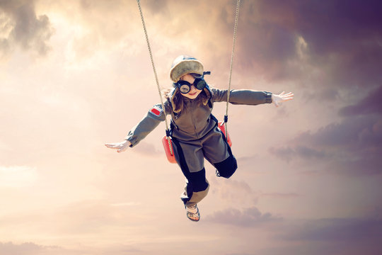 happy child girl wearing an aviator outfit swinging and flying deep in a sunset sky - positive future, dreams, destinations, vacations, concept