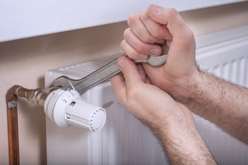 Fototapeta Męskie dłonie hydraulika trzymają płaski klucz którym odkręcają zawór regulujący temperaturę.
